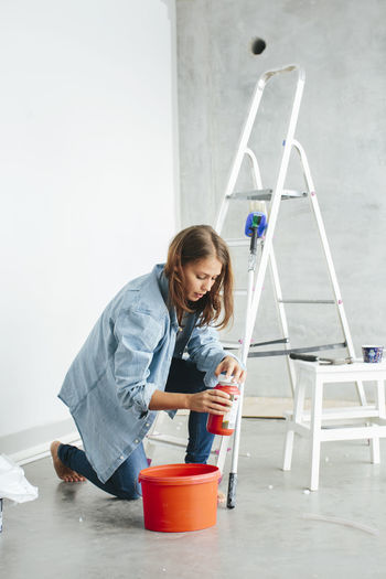 Full length of woman holding while standing on table at home