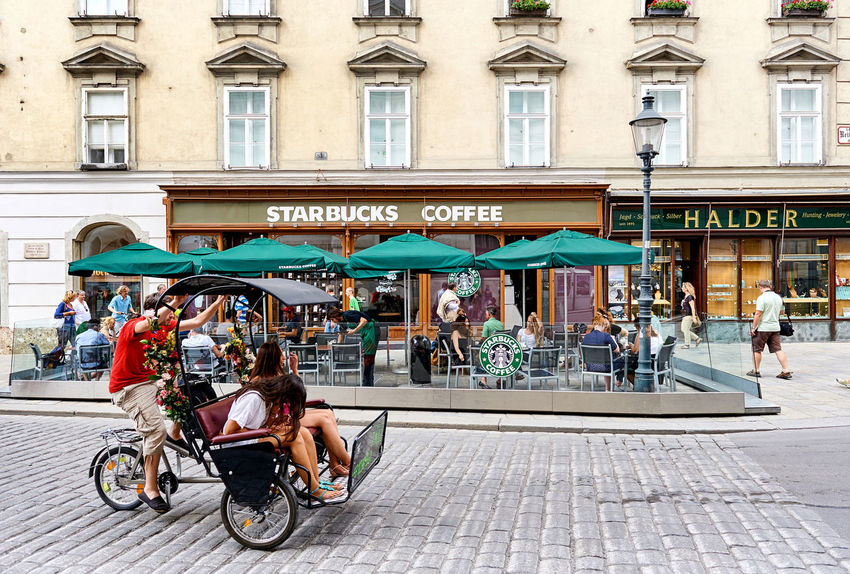 Vienna, Austria - August 7, 2012: Starbucks Coffee in the center of Vienna. Starbucks is the largest coffeehouse company in the world Open-air Cafe Austria Cafe City Center Coffee Coffeehouse Editorial  Europe Facades Holiday Outdoors People Shopfront Sidewalk Sidewalk Cafe Signboard Starbucks Coffee Street Summer Terrace Tourist Travel Destinations Urban Vacation Vienna