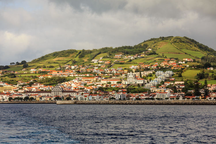 Scenic view of town by sea against sky