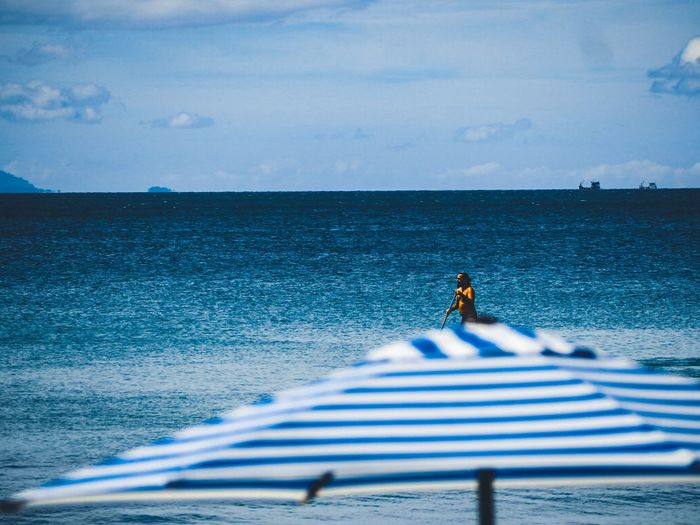 Mid distance view of mid adult man paddleboarding on sea against sky