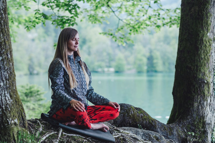 Young woman meditating while sitting in park