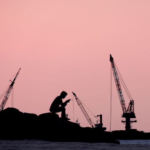 silhouette image of a man sitting in front of a book reading alone by the sea on pink background. Beauty In Nature Clear Sky Crane Crane - Construction Machinery Day Drilling Rig Industry Men Nature Nautical Vessel Occupation Offshore Platform Oil Pump One Person Outdoors People Real People Silhouette Sky Sunset Technology Water Waterfront Working