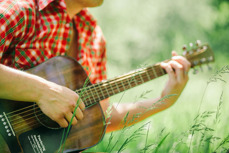 man playing guitar outdoors in park at summer Music Musical Instrument String Instrument Playing One Person Musical Equipment Real People Leisure Activity Lifestyles Arts Culture And Entertainment Day Village Countryside Authentic Moments Guitar Music Plucking An Instrument Musician Artist