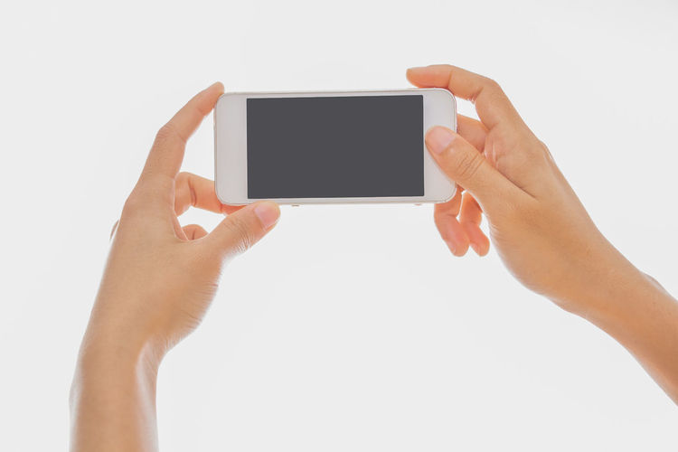 Midsection of person holding mobile phone against white background