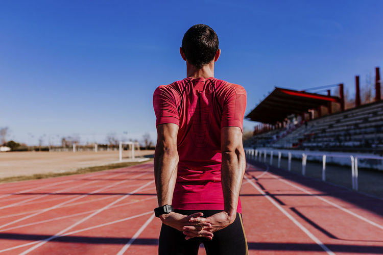 Rear view of athlete exercising on sports track
