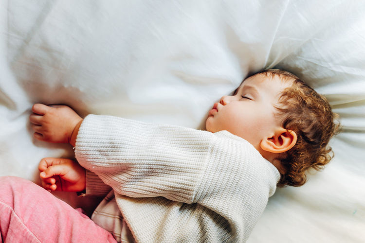 High angle view of baby girl sleeping on bed a home