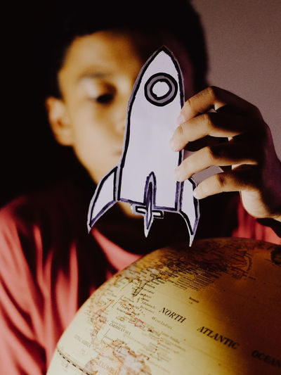 Close-up of boy playing a space ship card next to a earth globe
