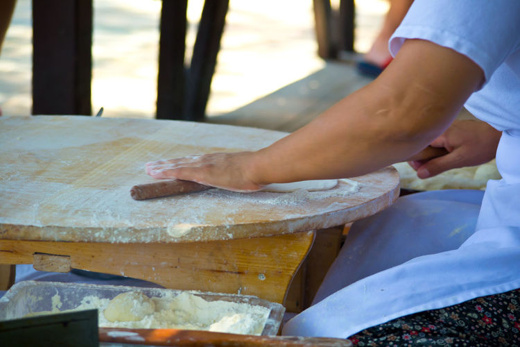 Cropped Hands Of Woman Rolling Dough