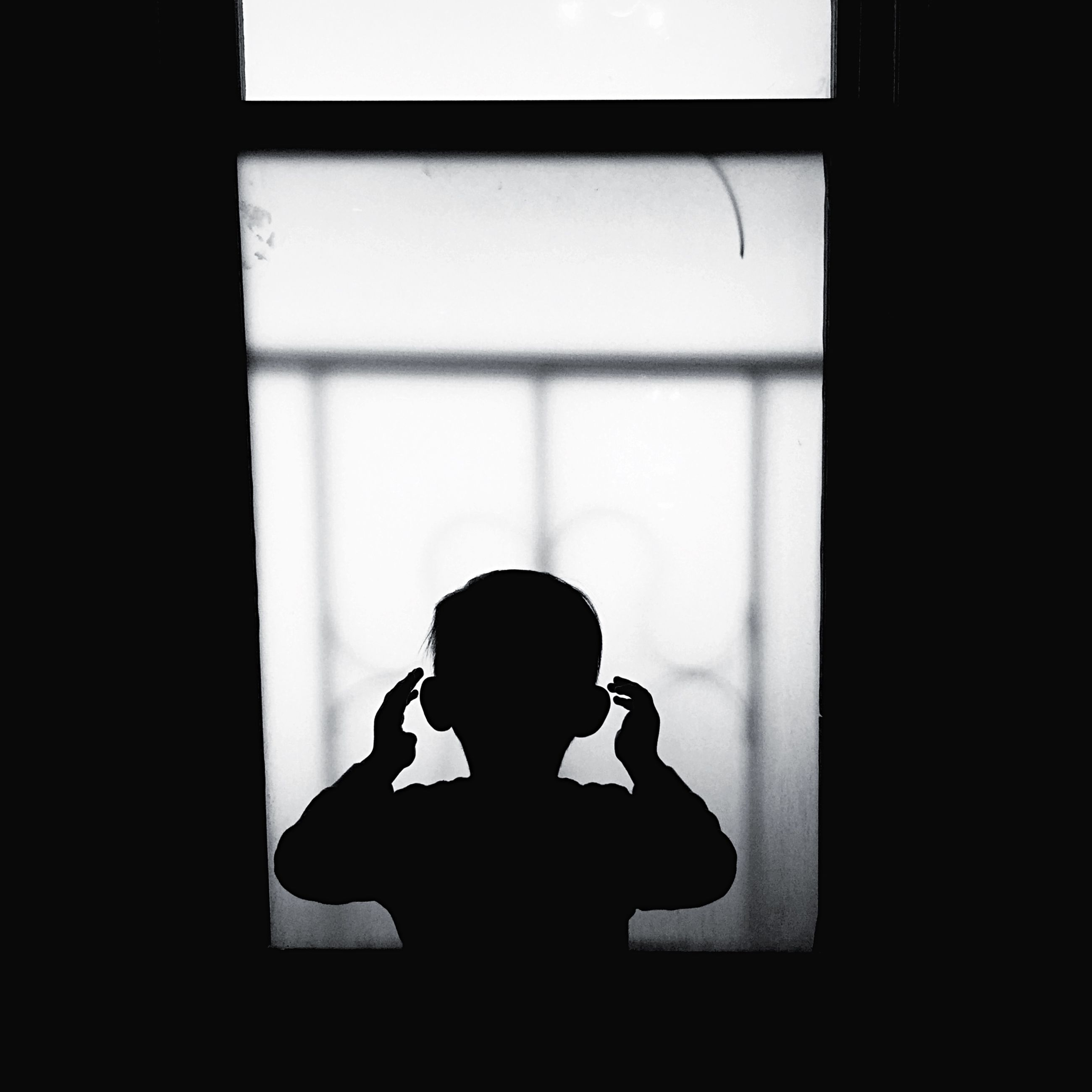 indoors, window, home interior, silhouette, dark, technology, sitting, lifestyles, men, wireless technology, holding, photography themes, wall - building feature, communication, shadow, darkroom, domestic room, copy space
