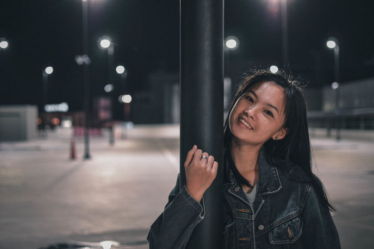 Portrait of smiling young woman by pole in city at night