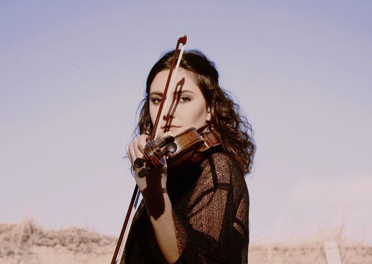 Portrait of young woman playing violin against clear sky