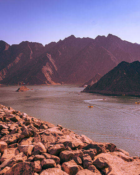 Scenic view of hatta lake and mountains against clear sky