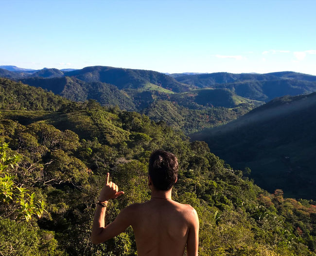 Rear view of shirtless man gesturing shaka sign against mountains