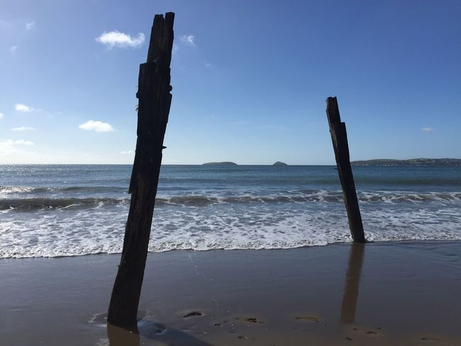 Beach Wooden Post Sea Water Tranquil Scene Scenics Tranquility Pole Wood - Material Shore Beauty In Nature Nature Sky Blue Wave Solitude Non-urban Scene Mountain Outdoors Remote