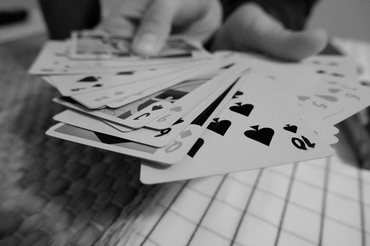 Close-up of person hands holding playing cards on table
