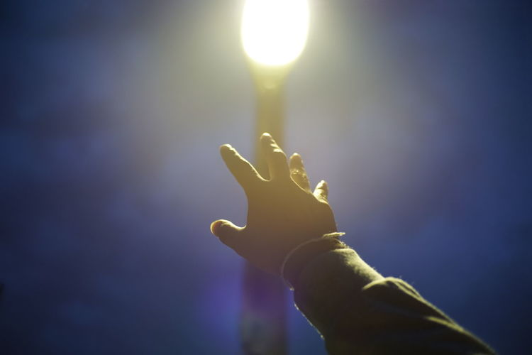 Cropped hand of person gesturing against illuminated light and sky