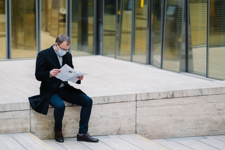 Full length of businessman wearing mask reading newspaper while sitting outdoors