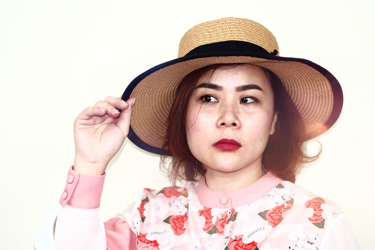 Woman wearing hat while looking away against white background