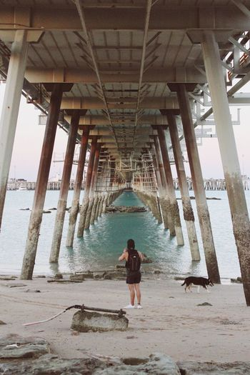 The tide is kind. Underneath Pier Architecture Water Bridge - Man Made Structure Sea Below Rear View Beach Architectural Column Built Structure Full Length One Person Day Indoors  Young Adult Under Adult People
