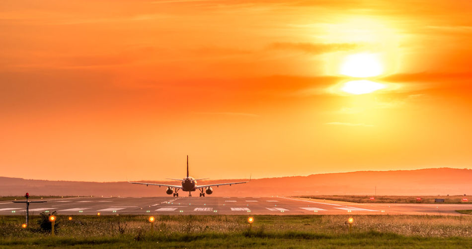 Airplane on runway against sky during sunset