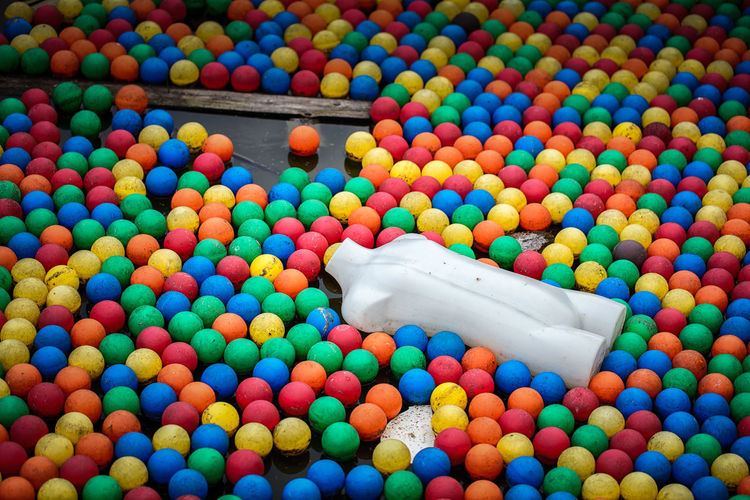 Mannequin amidst colorful balls