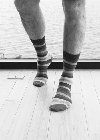 Mans legs showing him wearing striped socks standing by sea view window vertical portrait black and white. Adult Bare Dating Relationship Adult Affair Cheating Close-up Day Feet Hairy  Human Body Part Human Leg Indoors  Legs Low Section Male Masculine Morning After One Person People Purple Real People Socks Striped