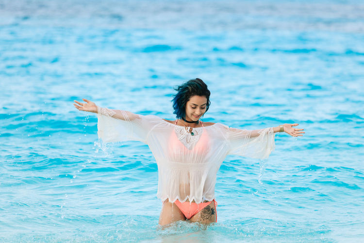 Portrair of a young girl at the beach Adult Adults Only Arms Outstretched Day Front View Full Length Leisure Activity Nature One Person Outdoors People Real People Sea Standing Water Young Adult Young Women