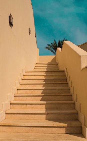 Steps Leading Towards Sea Against Blue Sky