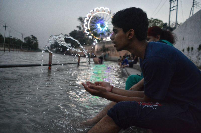 Side view of teenage boy splashing water while sitting at river