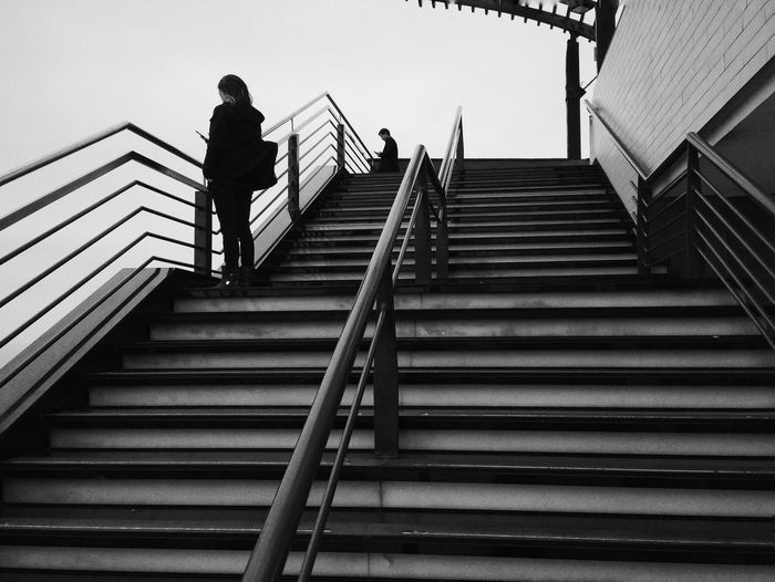 Low Angel View Of People Standing On Staircase Against Sky
