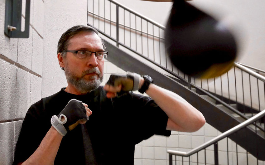 Senior man practicing boxing at gym