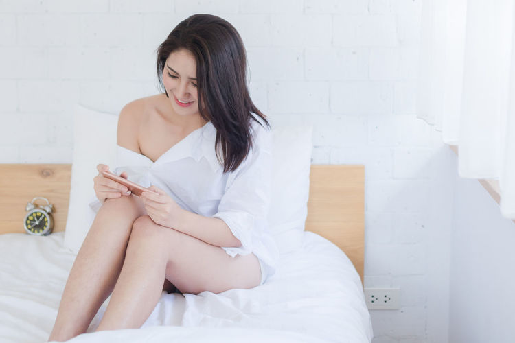 Woman Using Mobile Phone While Sitting On Bed At Home