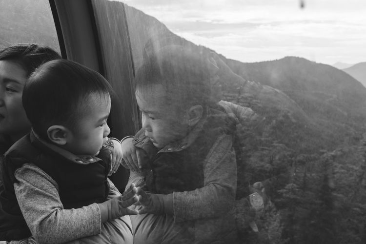 Cute baby by mother reflecting on overhead cable car window
