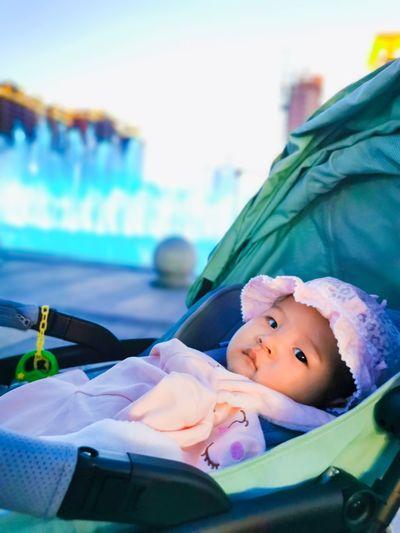 Portrait of cute baby girl lying in stroller
