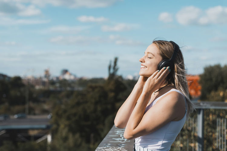 Side view of smiling young woman listening music by railing against sky