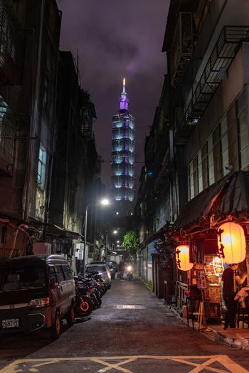 Architecture Building Exterior Built Structure City Building Night Illuminated Street Transportation Mode Of Transportation Motor Vehicle Car Incidental People Sky Residential District Land Vehicle Office Building Exterior Outdoors Nature City Life Skyscraper Taipei 101 Alley