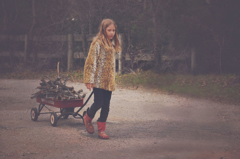 Full length portrait of girl pulling push cart with firewood on road