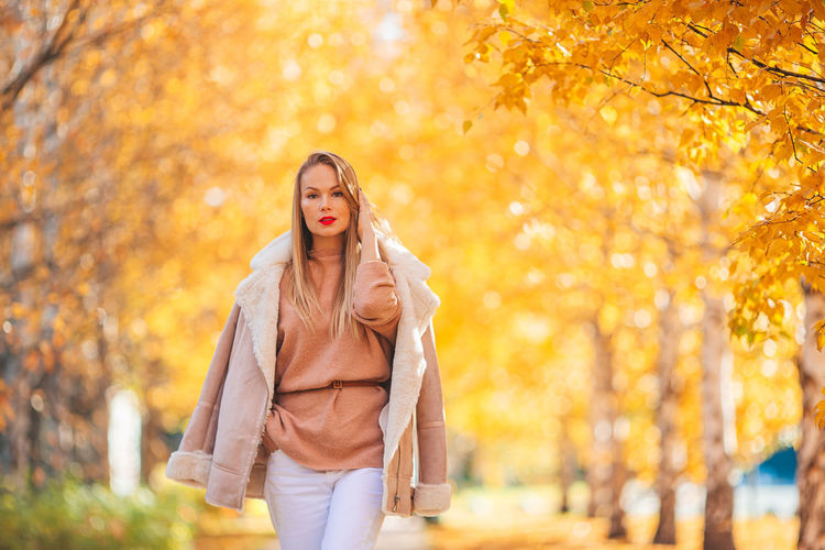 Portrait of a young woman standing in autumn