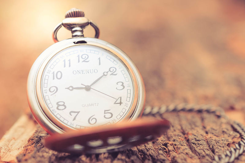 Close-up of pocket watch on wood