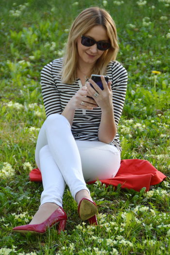 Full Length Of Young Woman Using Phone While Sitting On Grassy Field