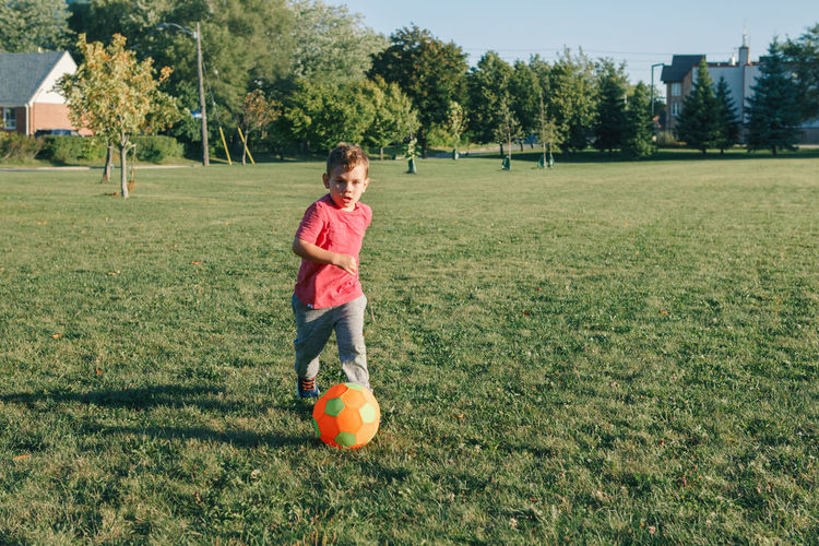 Boy playing with ball on grassy land in park