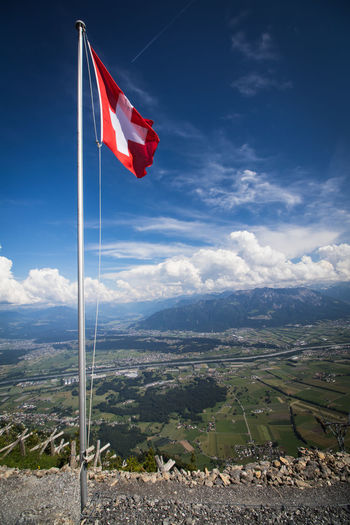 Beauty In Nature Cloud - Sky Day Environment Flag Landscape Mountain Mountain Peak Mountain Range Nature No People Non-urban Scene Outdoors Patriotism Red Scenics - Nature Sky Switzerland Tranquil Scene Tranquility Wind