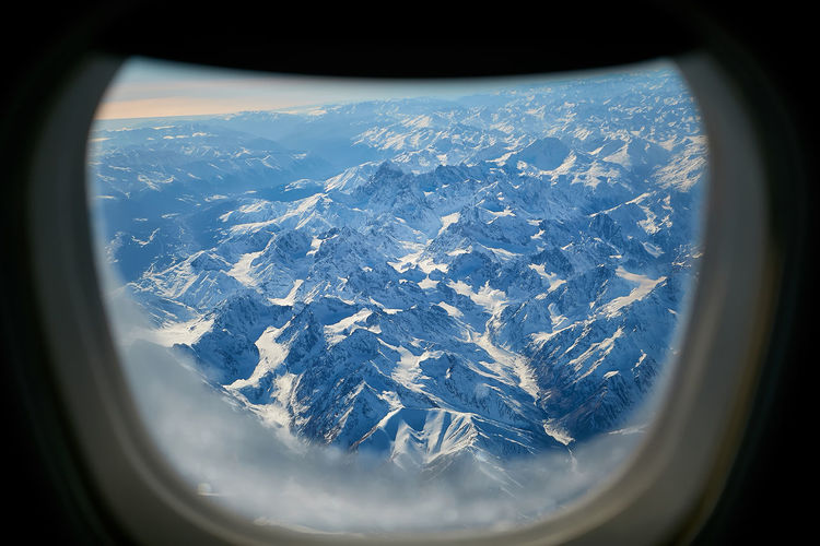 Aerial view of snowcapped mountains seen through airplane window