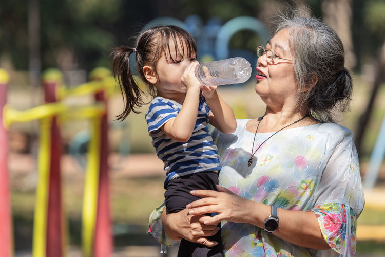 Cheerful grandmother with granddaughter drinking water