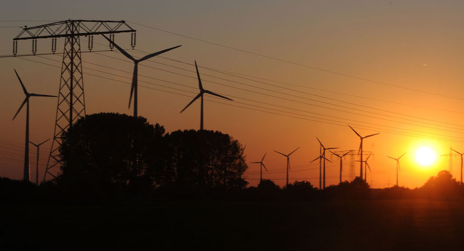 Silhouette windmills during sunset