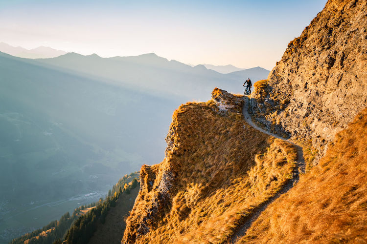 Man cycling on mountain road against sky
