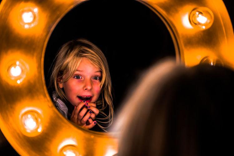 Cute girl reflecting in illuminated mirror