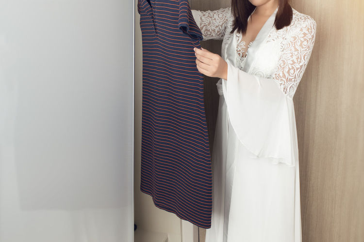 Asian woman in long white nightgown choosing clothes in wardrobe at home Standing One Person Women Midsection Indoors  Real People Adult Dress Clothing Holding Home Interior Lifestyles White Color Wall - Building Feature Casual Clothing Leisure Activity Fashion Pattern Day Hairstyle