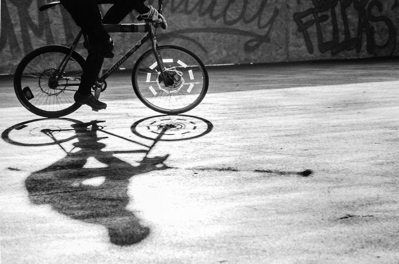 Low section of person with bicycle on shadow
