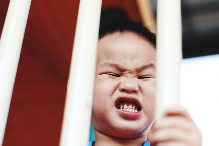 Angry boy seen through railing